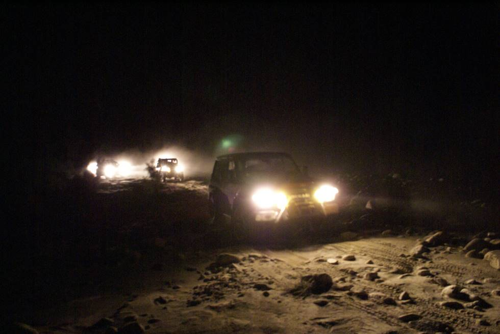 Offroading at night. The vehicles are staying within visual range of each other, because if you lose the track, then you are truly lost.